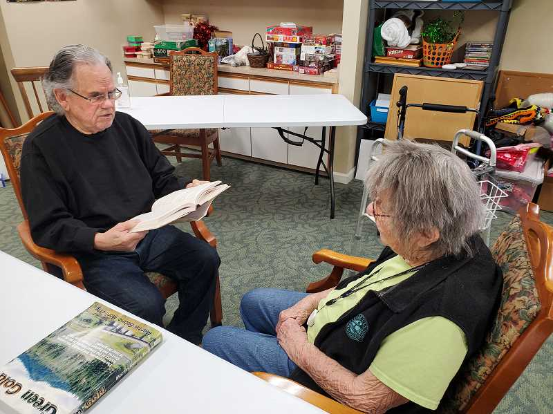 PHOTO COURTESY OF MARTIN MORISETTE  - Martin Morisette reads a book by Wilbur Smith to a resident at Carriage House on Thursday morning. Reading is one of Morisette's passions.