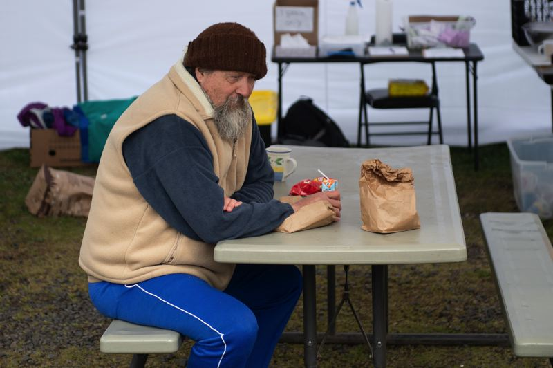 PMG PHOTO: CHRISTOPHER OERTELL - An unhoused man named Will eats a sack lunch at Open Door Counseling Center's day center in Cornelius on Thursday, March 26.
