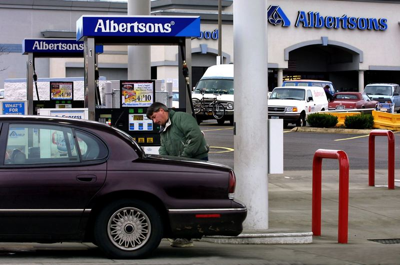 FILE PHOTO - Phil Covington pumps gas at Albertsons at their Prescott Street store in 2010.