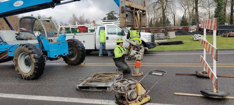 PMG PHOTO: SHANNON O. WELLS - A crewmember with Salem-based Carter & Co., works on a piece of heavy equipment used on the $1.8 million ODOT project to replace the old wooden walkway on the Troutdale Bridge and upgrade other safety features on the bridge.