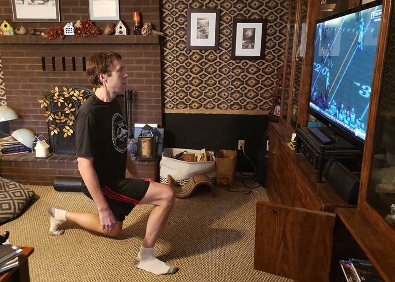 CONTRIBUTED PHOTO - Eastwind Running Club member Scott Pesznecker does some stretching while watching the replay of an historic Oregon Ducks football game.