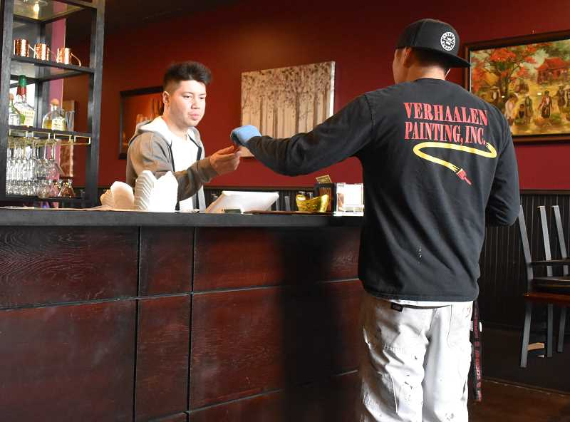 PMG PHOTO: RAYMOND RENDLEMAN - Clackamas resident David Le, an employee at Pho Thi in downtown Oregon City, takes a credit card for a to-go order on March 24.