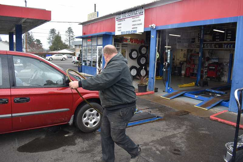PMG PHOTO: RAYMOND RENDLEMAN - Roy Binan, an employee at Luis Tire Service in Oregon City, helps an elderly driver keep her tires inflated so she can reach a doctor's appointment on March 24.