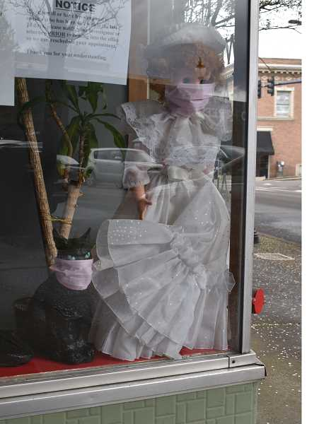 PMG PHOTO: RAYMOND RENDLEMAN - Virtus Group Investigations made face masks for its window-display dolls on Main Street in Oregon City.
