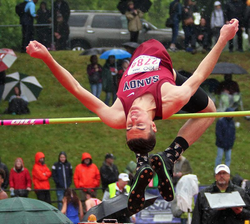 PMG PHOTO: DAVID BALL - Sandy High graduate Jackson Staples goes over the high jump bar during last years state track meet, while fans stand on the grassy hill surrounding the end zone.