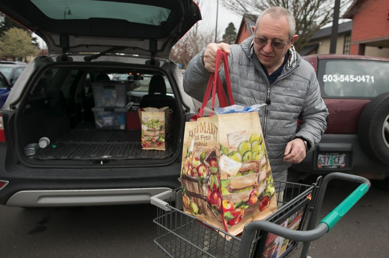 PMG PHOTO: JAIME VALDEZ - Mike Shmulevsky, owner of Sofia's Home, unloads groceries he bought from Fred Meyer into this car for the residents at his assisted living center in Wilsonville.