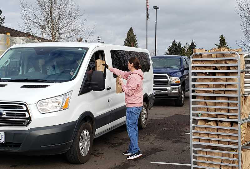 COURTESY PHOTO: LESLIE ROBINETTE - Gladstone Custodian Melissa Clark distributes grab-and-go meals to families in the drive-through lane.