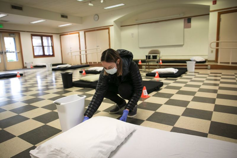 PMG PHOTO: JAIME VALDEZ - Megan Cohen, Beaverton community services coordinator, makes one of the beds at the city shelter at the Beaverton Community Center. Starting today, March 30, the shelter will be open until May 31.