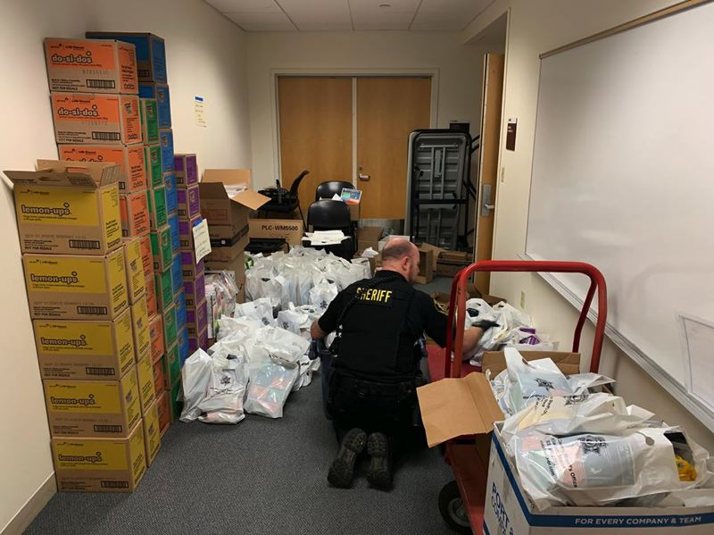 COURTESY PHOTO: WASHINGTON COUNTY SHERIFF'S OFFICE - A deputy with the Washington County Sheriff's Office organizes 'personal assistance care kits' for unhoused people as part of outreach amid the coronavirus outbreak.