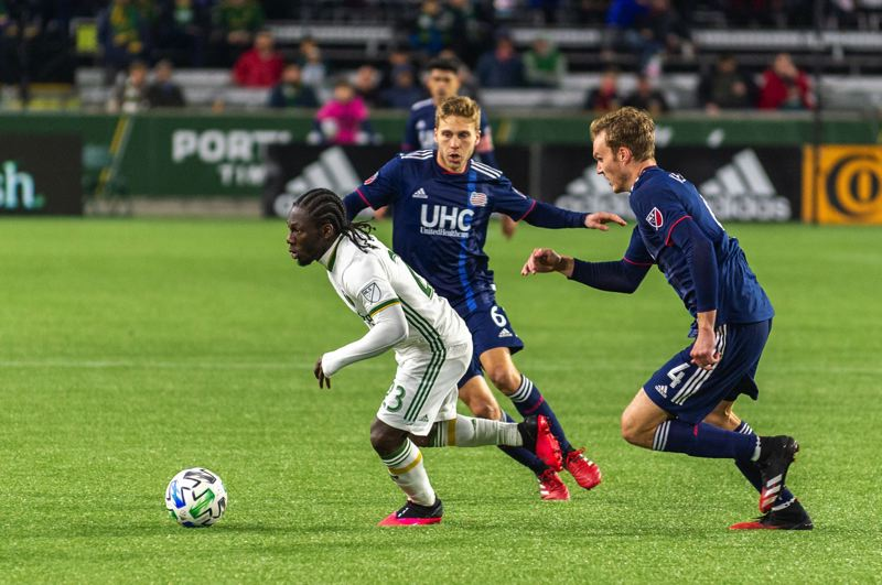 COURTESY PHOTO: DIEGO G. DIAZ - Portland Timbers midfielder Yimmi Chara (left) eludes the mark of New England players Scott Caaldwell and Henry Kessler during a 3-1 loss to the Revolution on Feb. 22 at Providence Park.
