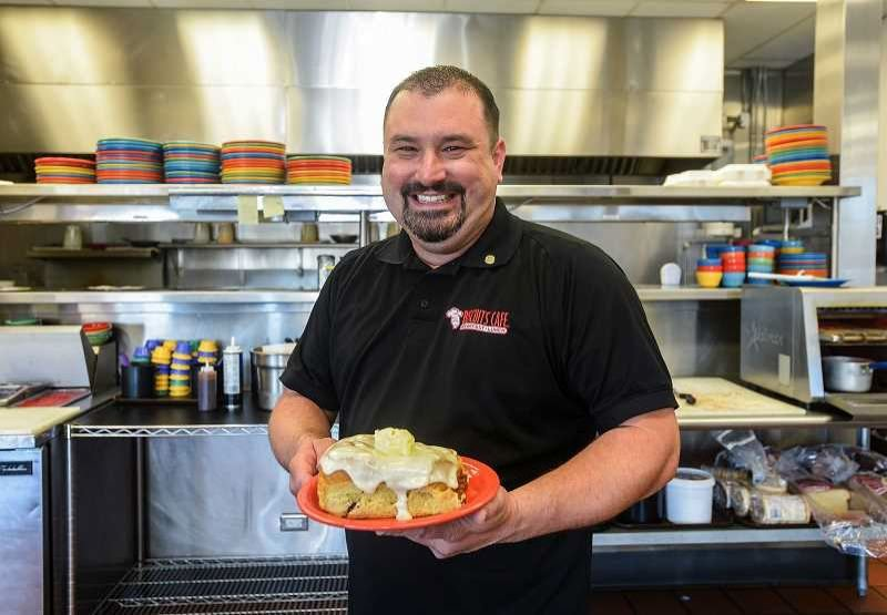 PMG FILE PHOTO - David Ligatich, owner of Gresham Biscuits Cafe, shows off one of his restaurants famed cinnamon rolls, likely one of the items available from the eaterys take-out-only menu.