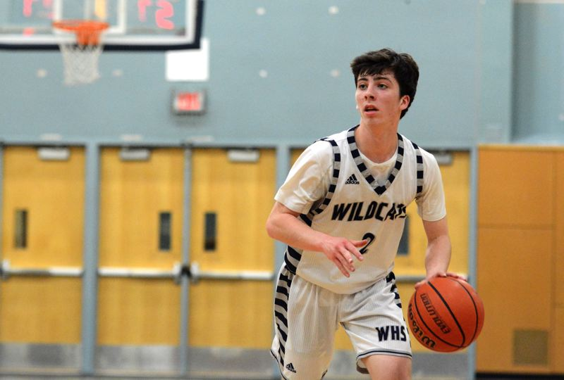 PMG PHOTO: DEREK WILEY - Wilsonville senior Finlay Dunn dribbles the ball during the 2019-20 basketball season.