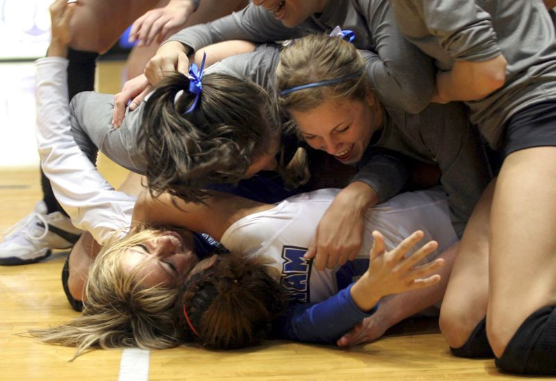 PMG FILE PHOTO: DENISE FARWELL - Gresham High volleyball legend Lori Cook gets buried under the pile after coaching the Gophers to a state title in 2006. She played on Greshams undefeated team in 1989 during a string of four consecutive state titles for the Gophers.