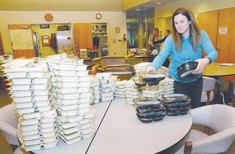 NEWBERG GRAPHIC PHOTO: GARY ALLEN - Stephanie Meyer, a volunteer for Newberg Meals on Wheels for about year, unboxes the frozen 'weekend meals' that will be delivered to homes throughout the area.