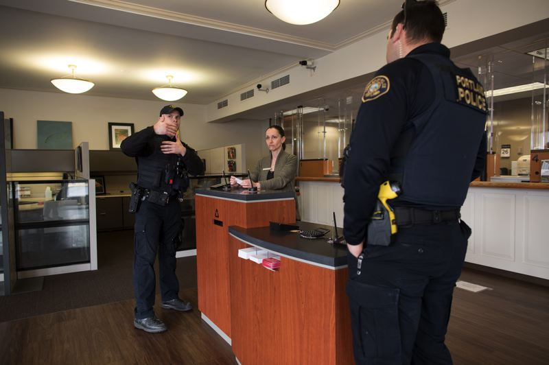 PMG PHOTO BY JAIME VALDEZ - Portland Police have been working to educate people about social distancing. Here, two Portland neighborhood officers speak with a bank employee.