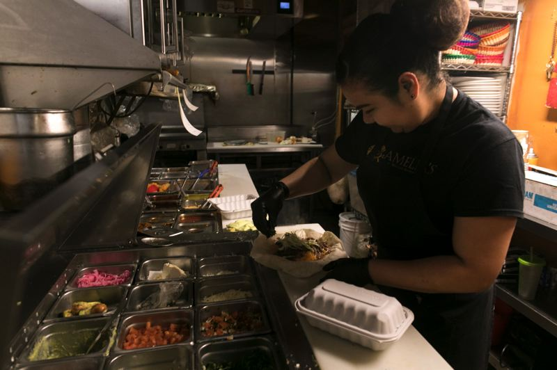 PMG PHOTO: JAIME VALDEZ - Maricela Garcia, a cook at Amelia's Exquisite Mexican Dining, makes a burrito for a customer for a lunch takeout.
