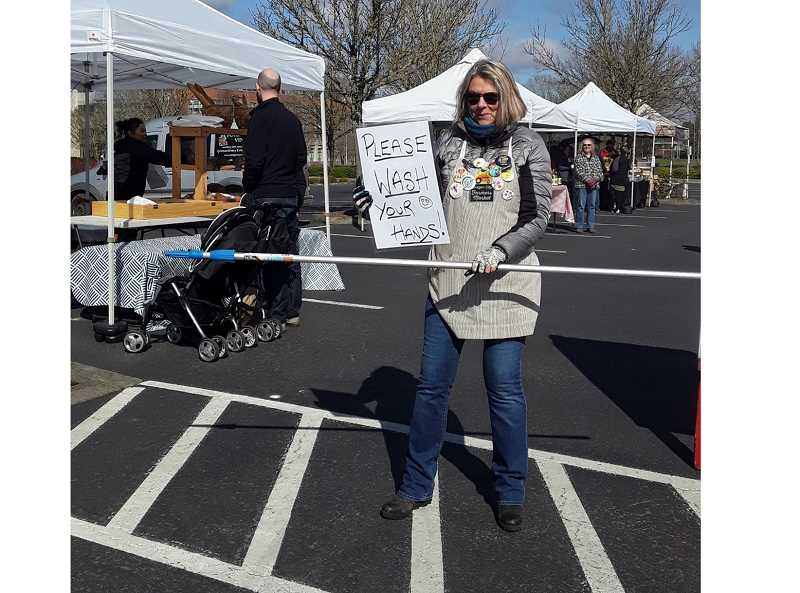 COURTESY PHOTO - Oregon City Market Manager Jackie Hammond-Williams encouraged customers to wash their hands and stay 6 feet from each other, demonstrating with the 6-foot pole at a recent market day.
