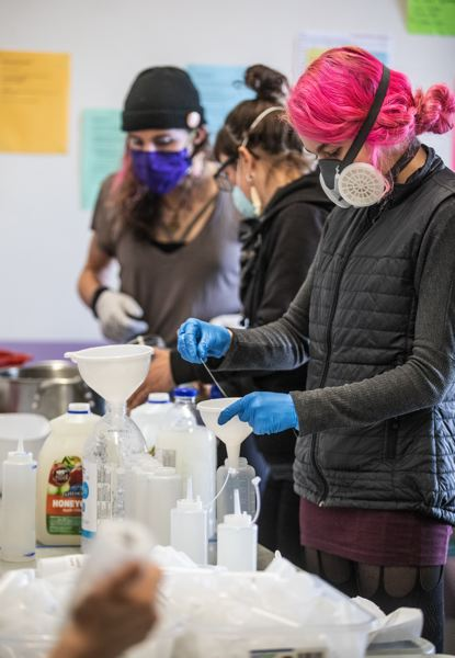 PMG PHOTO: JONATHAN HOUSE - Q Center volunteer McKenzie helps pour hand sanitizing solution on April 7 in Northeast Portland.