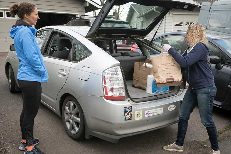 PMG PHOTO: JAIME VALDEZ - Jessica Pierce watches as Karin Calde load a bag of groceries for a family into her car. Pierce who works in the Beaverton School District is volunteering to deliver food to a family of need for a group that Calde organized on Facebook called Team Beaverton. The group helps those who are affected by the COVID-19 virus.