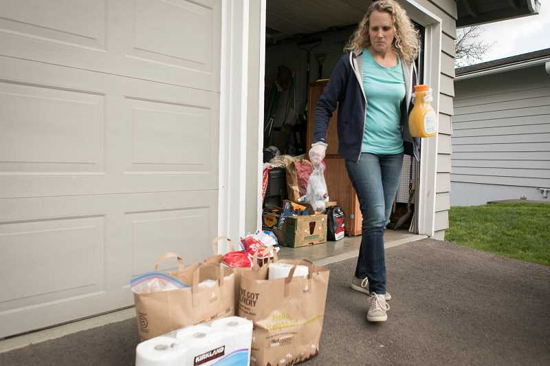 PMG PHOTO: JAIME VALDEZ - Karin Calde moves bags of groceries to be delivered to a family in Beaverton. Calde organized a Facebook group called Team Beaverton that helps those who are affected by the COVID-19 virus.
