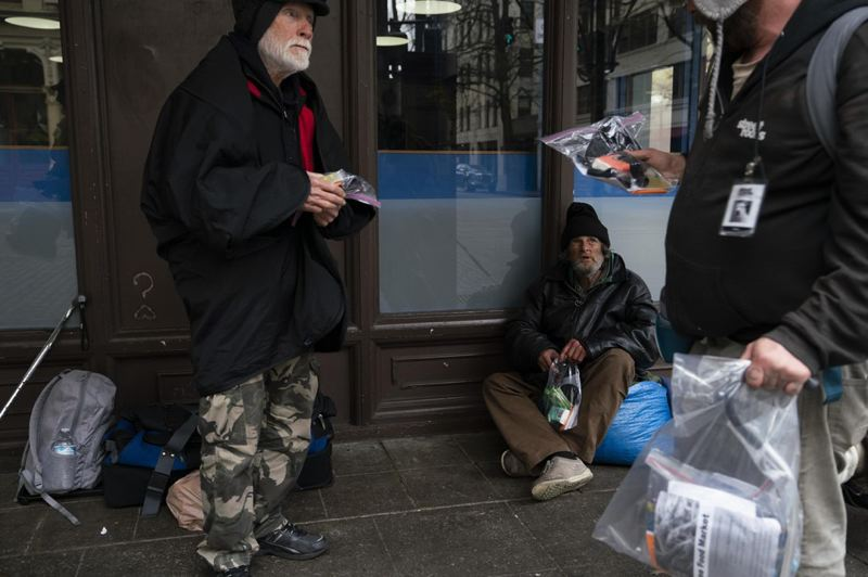 COURTESY PHOTO: JONATHAN LEVINSON/OPB - Mike Dusek, an unhoused person living in Portland, distributes hygiene supplies to other members of the unhoused community on March 28.
