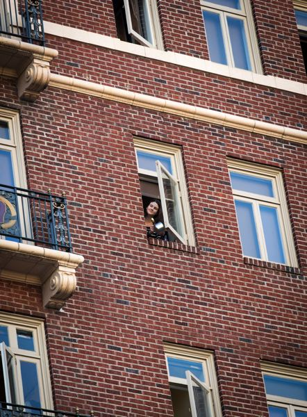PMG PHOTO: JAIME VALDEZ - A lady who lives in an apartment at the Sovereign Hotel in downtown Portland bangs her pan at 7 p.m. to honor frontline workers.