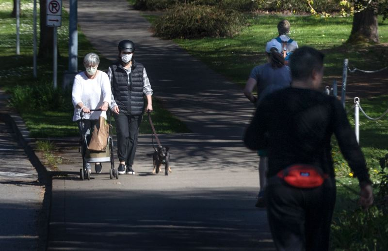 PMG PHOTO: JONATHAN HOUSE - Pedestrians with masks walk along Southeast Bybee Boulevard in Portland.