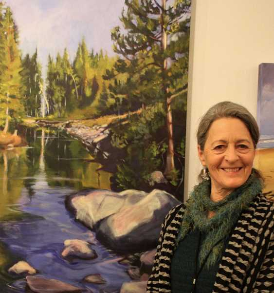 Lisa Wiser poses with one of her watercolor paintings. Visit lakeareaartists.com to view more of her art.