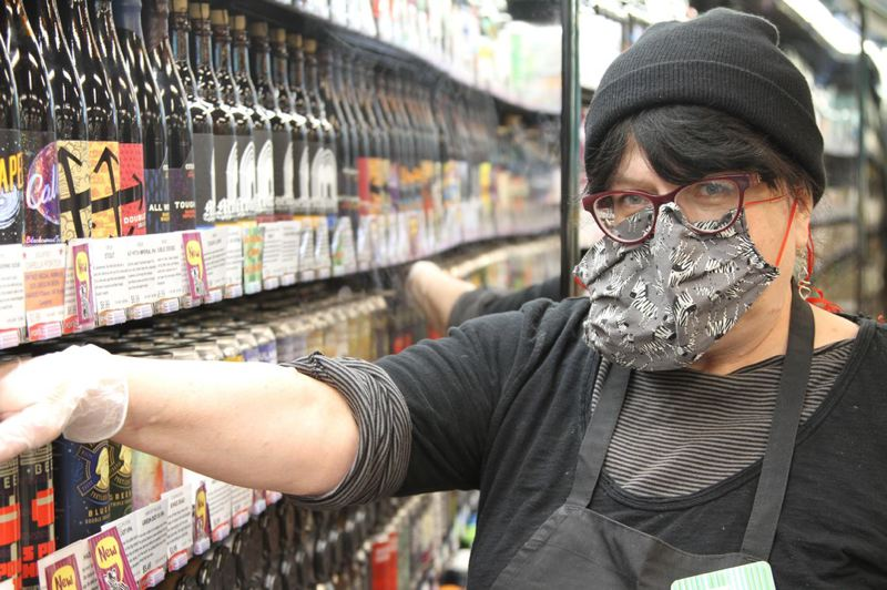 "COURTESY PHOTO: KRISTIAN FODEN-VENCIL/OPB - Patty Beavers wears protective gear at Green Zebra grocery in Southeast Portland, ""I'm just grateful that I'm able to work right now. … Just hang in there, be clean, be safe, this will pass. It always has and it will."""