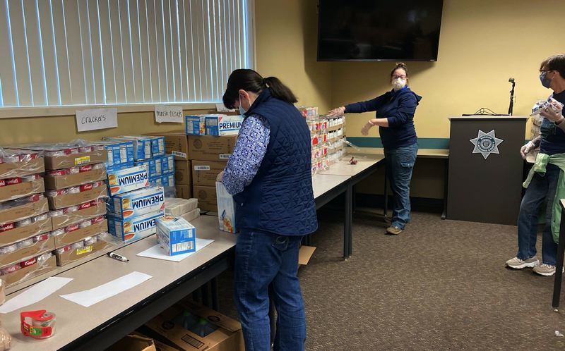 COURTESY OF CLACKAMAS COUNTY SHERIFF'S OFFICE - Clackamas County employees volunteer to package boxes of supplies to be delivered to local residents in need.