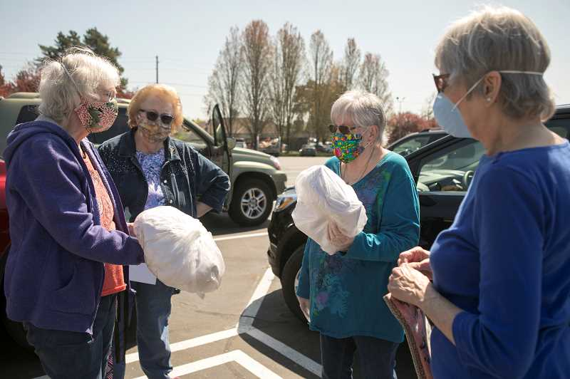 PMG PHOTO: JAIME VALDEZ - Michelle Faber, left, Judy Kilgore, Carol Springer and Shirley Schultz confer with one another about the masks they made for the Veterans Affairs Medical Center in Portland.