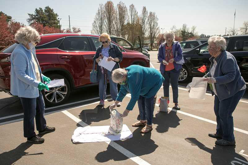 PMG PHOTO: JAIME VALDEZ - Kathy Chase, left, Judy Kilgore, Michelle Faber and Eleanore Mickus watch as Carol Springer unpack fabric that can be used to make masks for the Veterans Affairs Medical Center in Portland.