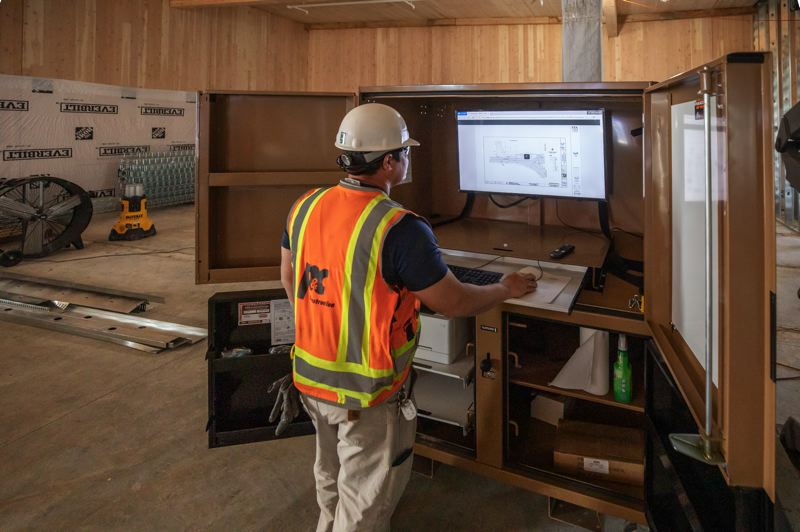 PAMPLIN MEDIA GROUP: JONATHAN HOUSE  - At the Robert Libke Public Safety Facility at 1232 Linn Avenue, a worker shows off the rolling big screen for viewing plans on Procore, so workers can social distance and don't have to huddle over an iPad any more.