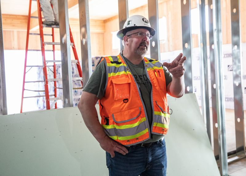 PAMPLIN MEDIA GROUP: JONATHAN HOUSE  - Project superintendent Brad Esler keeps his distance at the Robert Libke Public Safety Facility at 1232 Linn Avenue, while a worker shows off the rolling big screen for viewing plans on Procore. It took a few days to get used to but now the workers are encouraged to find creative ways to not get within six feet of each other.
