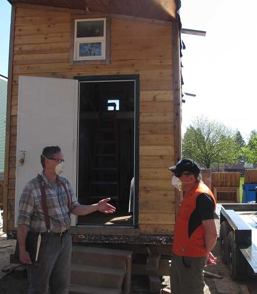 PMG PHOTO: BILL GALLAGHER - Cascadia Clusters co-executive directors Toma Solano, left, and Andy Olshin outside one of the 160-square-foot tiny houses under construction behind the field next to the Mittleman Jewish Community Center.