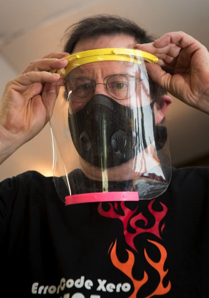 PMG PHOTO: JAIME VALDEZ - Marshall Stowell, a mentor with the Wilsonville robotics teams, applies a face shield that was made by members of the Wilsonville and West Linn robotics teams.