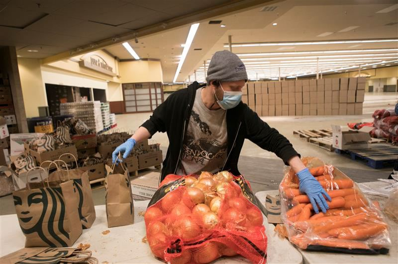 PMG PHOTO: JAIME VALDEZ - Morgan Winnick, an employee with Hood to Coast, packs produce to be included in a box for people of need at the Sunshine Division distribution center in SE Portland.