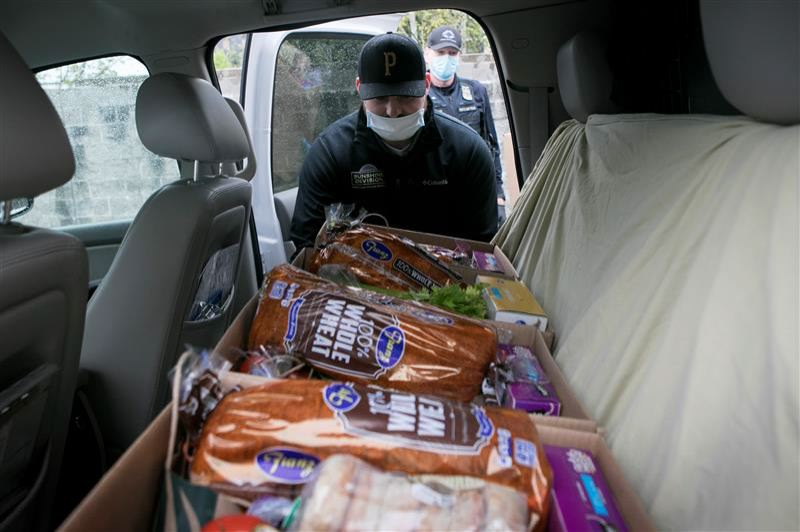 PMG PHOTO: JAIME VALDEZ - Tyler Kline, who recently was sworn in as an officer with the Portland Police Bureau, loads a box of food into the patrol vehicle of Portland police officer Derk Gulsvig on April 22 at the Sunshine Division distribution center in Northeast Portland.