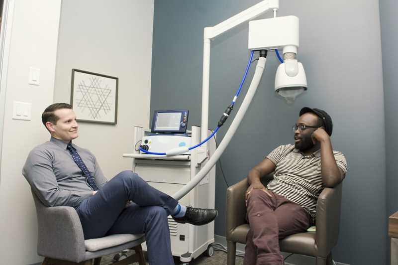 COURTESY PHOTO - Dr. Jonathan Horey, chief medical officer and co-founder of the Portland Active Recovery TMS clinic, talks with a patient.