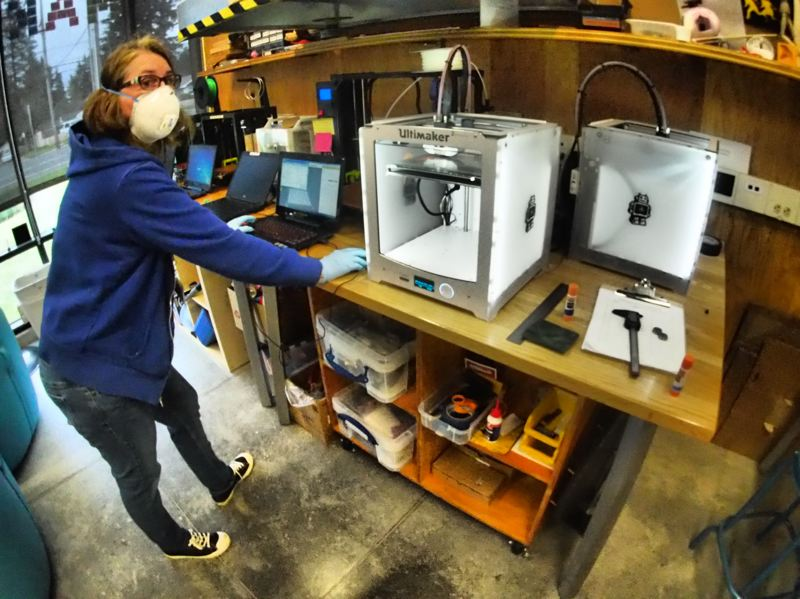 COURTESY PHOTO: MULTNOMAH COUNTY LIBRARY - Makerspace Program Specialist Desiree Wolcott-Cushman, with 3D printer, gets ready to make a face shield at the Rockwood Library makerspace.