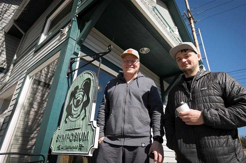 PMG PHOTO: JAIME VALDEZ - Kevin Bates, left, owner of Symposium Coffee in Tigard and Sherwood, and Jake Pflug, assistant manager, stand outside the Tigard location on March 16, the same day the governor banned dine-in, sit-down customers from bars and restaurants.