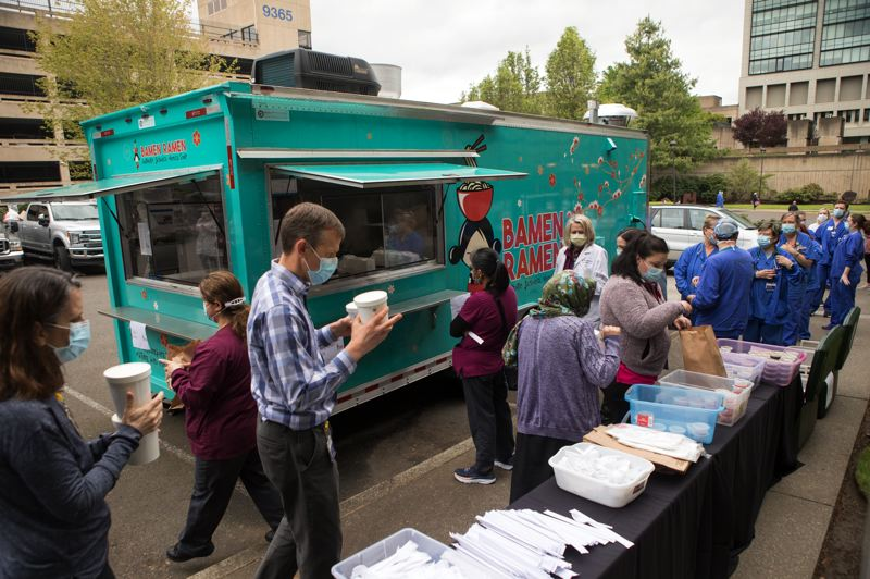 PMG PHOTO: JAIME VALDEZ - Healthcare workers at Providence St. Vincent Medical Center line up for noodles donated by the Bamen Ramen food truck April 24.