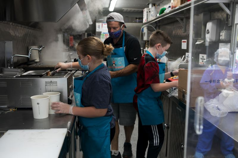 PMG PHOTO: JAIME VALDEZ - Jason Jewett, center, aided by his two children, Sami, left, and Jacob, prepare gyoza and ramen noodles in the family's Bamen Ramen food truck at Providence St. Vincent Medical Center last week. The family, who opened their restaurant in Forest Grove last fall, donated 500 bowls of ramen to healthcare workers.