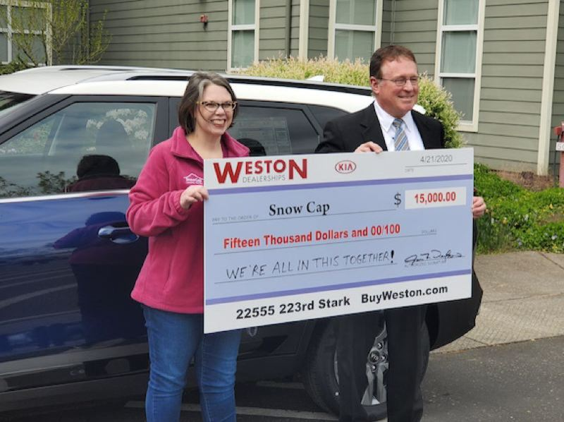 PMG PHOTO: STEVE BROWN - Jan Weston, owner and chief financial officer of Weston Kia, presented $15,000 each to SnowCap Community Charities and My Father's House. Pictured here is SnowCap Executive Director Kirsten Wageman.