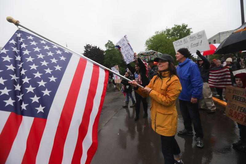 PMG PHOTO: AMANDA LOMAN - A woman waved an American flag during the 'Reopen Oregon' rally in Salem on Saturday, May 2.