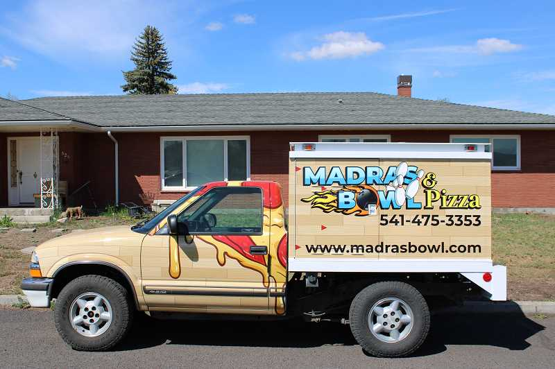 JENNIFFER GRANT/MADRAS PIONEER - Madras Bowl & Pizza has added delivery. RipQ wrapped the truck owner Christie Bouvia, her husband, Michael, and her daughter, Jenni Young, are using to deliver pizzas.