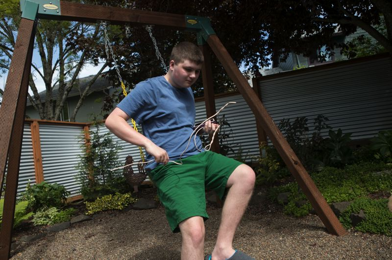 PMG PHOTO: JAIME VALDEZ - Henry Kottkey, a 15-year-old with autism who attends Oak Grove Academy in Forest Grove, on a swing set in his backyard.