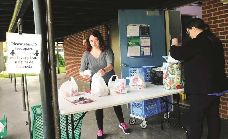 NEWBERG GRAPHIC: GARY ALLEN - Chehsea Shotts, an education assistance in the Mindfullness Room at Dundee Elementary School, distributes upwards of 140 lunches a day at the meal site adjacent to the Newberg School District administrative building.