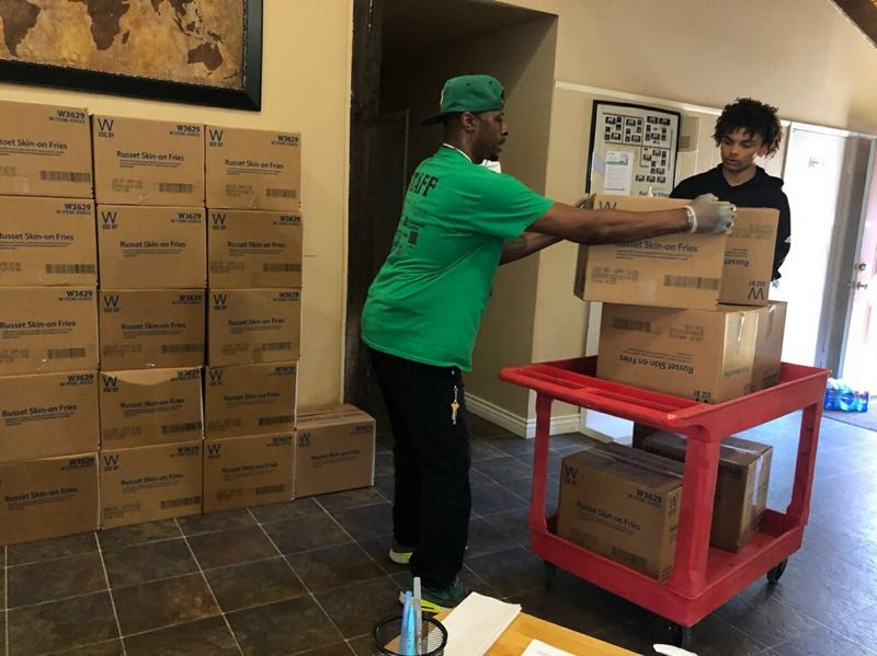 COURTESY PHOTO: PLAY GROW LEARN - Anthony Bradley, executive director of Play Grow Learn, helps deliver some of the family boxes.
