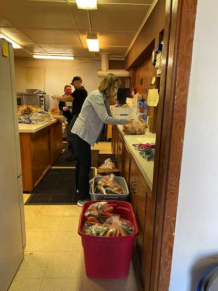 PMG PHOTO: HOLLY BARTHOLOMEW - Volunteers prepare bags of fresh produce at the West Linn Food Pantry.